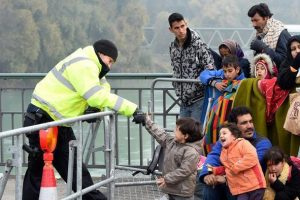 "A German police officer plays with a migrant boy how is waiting with a group of migrants to cross the Austrian-German border at the ""Innbruecke"" bridge near the Austrian village of Braunau and the German village Simbach am Inn, southern Germany, on October 28, 2015. AFP PHTO / CHRISTOF STACHE        (Photo credit should read CHRISTOF STACHE/AFP/Getty Images)"
