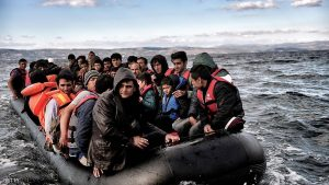 Refugees and migrants sail towards the Greek island of Lesbos on October 25, 2015 as they cross the Aegean sea from Turkey.  At least three migrants -- two children and a woman -- drowned when their boat sank off the Greek island of Lesbos, the coastguard said, the latest fatalities in Europe's refugee crisis. Around a dozen others, mostly Afghans, are still missing after the rickety vessel, carrying 60 people, went down at dawn as it made the perilous crossing from Turkey, according to the Greek coastguard. AFP PHOTO / ARIS MESSINIS        (Photo credit should read ARIS MESSINIS/AFP/Getty Images)