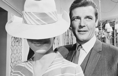 English actor Roger Moore on the set of the British TV series, 'The Saint', with model Angela Fountain, at Associated British Elstree Studios in Hertfordshire, 22nd February 1967. The are filming the episode, 'A Double In Diamonds'. (Photo by Mike McKeown/Daily Express/Hulton Archive/Getty Images)