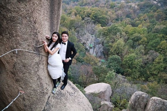 PROD-Newlywed-Couple-Poses-For-Wedding-Photos-On-Cliff-Face-In-Zhumadian